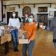 Verena Rohde (links) und Bastian Rütten füllen mit einigen Helfern die 180 Pakete im großen Saal des Priesterhauses. (Foto: Bistum Münster / Christian Breuer)